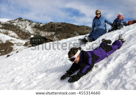 Motion blur of a little girl (age 6) slide on snow while here mother and sister watching. Winter travel vacation holiday concept. copy space - stock photo