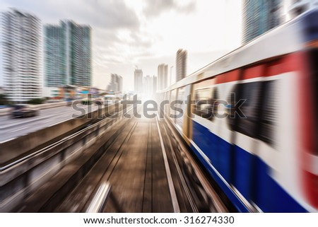 Motion blur of a train  from outside a moving monorail in Thailand. - stock photo