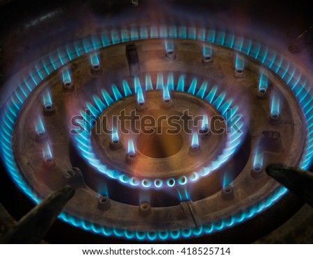 motion blur of burning blue gas on gas burner with shadow edge - stock photo
