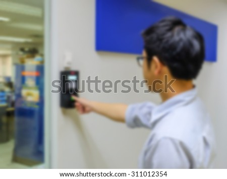 Motion blur of employee come to work by finger scan - stock photo