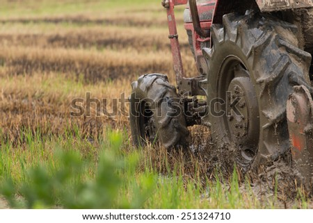 Motion blur of wheel tractor while working on farms. - stock photo