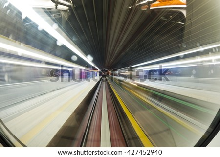 Motion blur on speeding train Train is pulling out fast from station at night. Motion blurred platforms, tracks and metal roof.