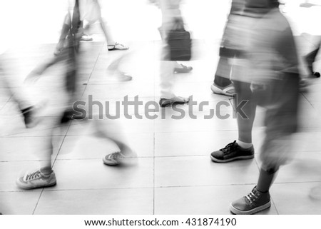 Motion blur people walking on white tiled floor. They are hurry in rush hour. Black and white filter - stock photo