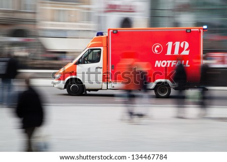 motion blur picture of a driving ambulance vehicle in the city - stock photo