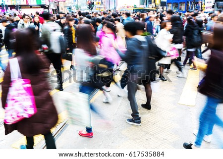 motion blur picture of crowds of people crossing a busy street in Hong Kong