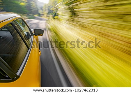 Motion blur shot of a car driving fast in the curve on mountain road