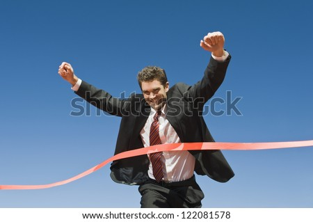 Motion blur shot of a cheerful businessman crossing the finish line of racing track against blue sky - stock photo