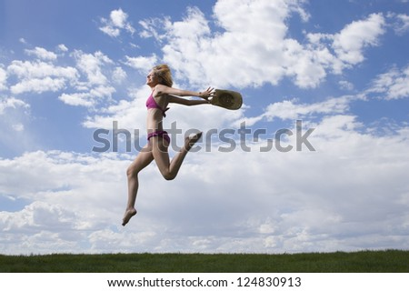 Motion blur shot of a young woman jumping against cloudy sky