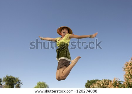 Motion blur shot of an Asian woman jumping with arms outstretched against blue sky
