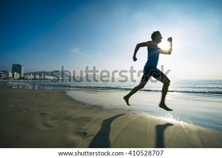Motion blur silhouette of an athlete running with sport torch on Copacabana Beach in Rio de Janeiro, Brazil