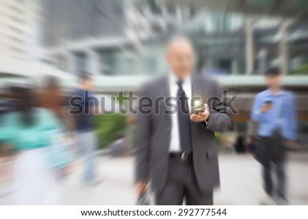 motion blur suit and tie businessman hand on mobile phone with small circle light ball effect over phone - stock photo