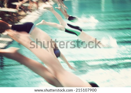 Motion blur swimmers diving into a pool during a race - stock photo