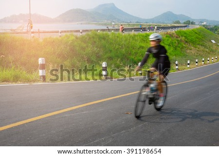 Motion blur woman riding bicycle along the lake side road in Thailand
