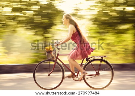 motion blur. young woman in a dress rides a bike in a summer park. Active people. Outdoors - stock photo