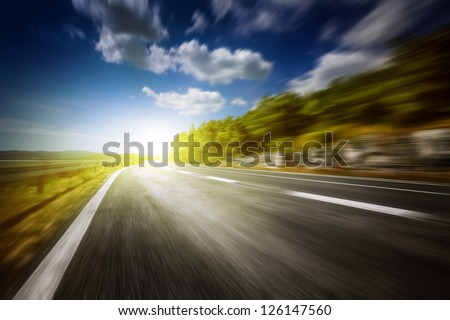 Motion blurred asphalt road - stock photo