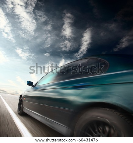 Motion blurred car on road and sky with clouds - stock photo