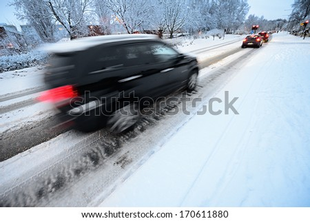 Motion blurred car on winter road in traffic - stock photo