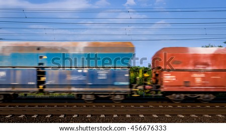 Motion blurred cargo train cars, petrol - red, blue sky, white clouds.