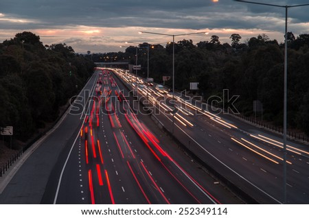 Motion blurred cars and trucks driving along a suburban freeway at dusk in Melbourne, Australia, their lights leaving red and white light trails. - stock photo