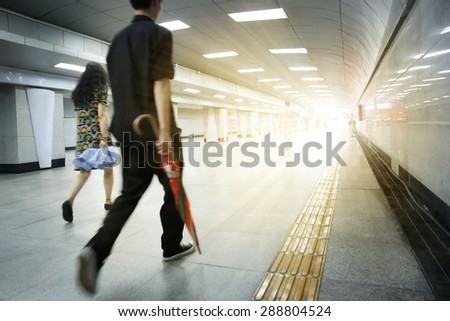 Motion blurred commuters walking in subway station. - stock photo