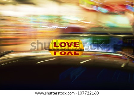Motion blurred conceptual image of a taxi sign on the roof of a car with the word Love on it - stock photo