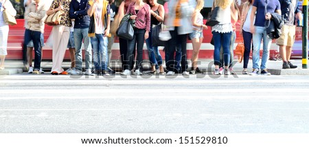 Motion blurred crowd waiting to cross street - stock photo