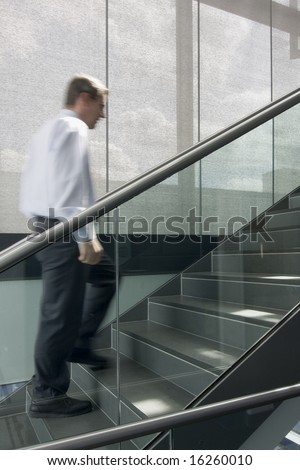 Motion blurred image of businessman climbing a stairway in an office building - stock photo