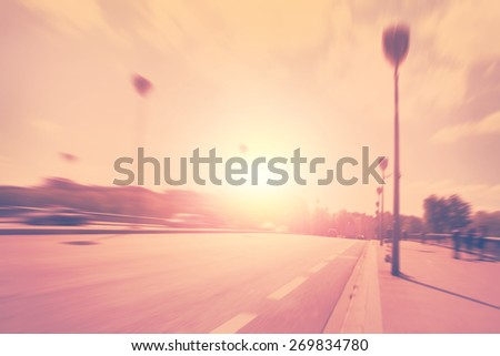 Motion blurred image of city street at sunset. - stock photo