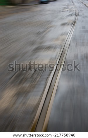 Motion blurred image of old tramway track on paved road - stock photo