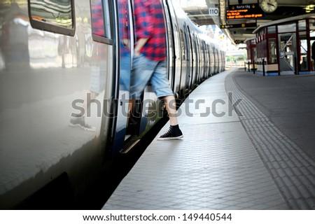 Motion blurred man entering train - stock photo