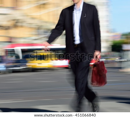 Motion blurred man in suit crossing street - stock photo
