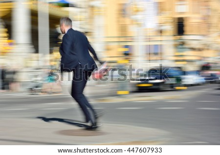 Motion blurred man in suit running to cross street