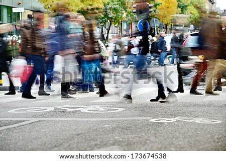 Motion blurred pedestrians on zebra crossing - stock photo