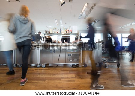 Motion blurred people at lunchtime in a busy canteen - stock photo