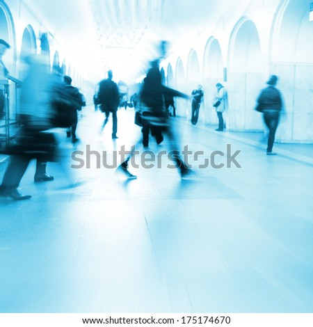Motion blurred people walking in subway station. - stock photo