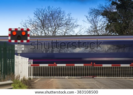 Motion blurred train speeding through a level crossing - stock photo