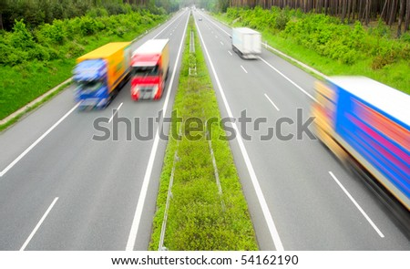 Motion blurred trucks on highway. - stock photo