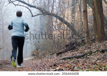 Motion blurred woman running in foggy winter morning - stock photo