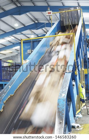 Motion of rubbish on conveyor belt in recycling factory - stock photo