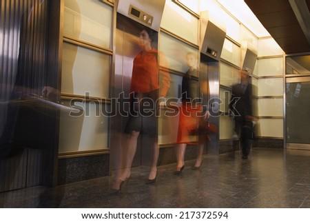 Motion shot of businesspeople walking past elevators - stock photo
