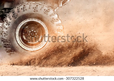 Motion the wheels tires and off-road that goes in the dust of the desert through the wheels on the sand - stock photo