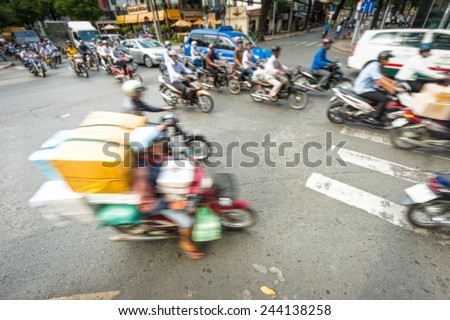 Motion view of street in Vietnam. Southeast Asia. Busy daily traffic with stream of motorbikes and cars. Blurry view of weighted scooter in foreground. Transportation and traffic. - stock photo