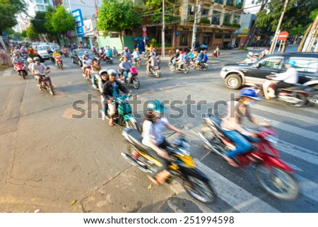 Motion view of street in Vietnam. Southeast Asia. Busy daily traffic with stream of motorbikes and cars. Blurry view of bikes in foreground. Transportation and traffic.