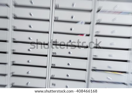 Motion zoom effect of a lot of metal mail boxes inside residential buildings - stock photo