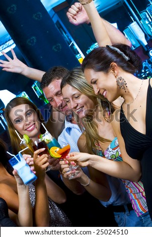 Motioned portrait of young attractive people having fun in night club - stock photo