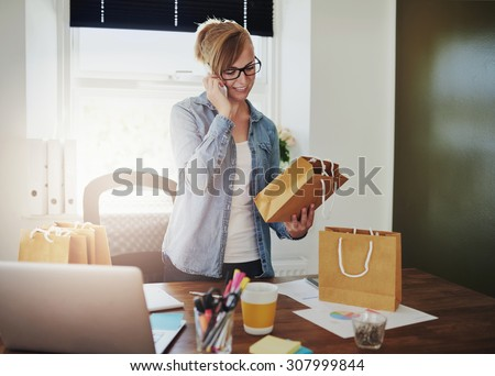 Motivated businesswoman placing orders on the phone for the packaging for her new online web based store as she holds a brown paper gift bag in her hand - stock photo