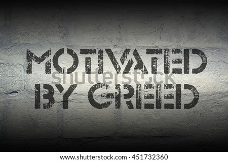 motivated by greed stencil print on the grunge white brick wall - stock photo