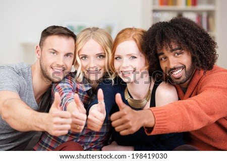 Motivated enthusiastic young multiracial business team posing with their heads close together giving a thumbs up gesture of approval and success - stock photo