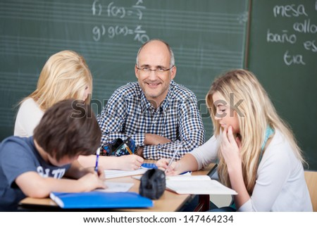 Motivated male teacher with his students sitting at a table together in a group discussion - stock photo