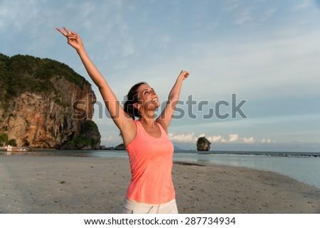 Motivated sporty woman celebrating workout success at the beach, Krabi, Thailand. Female athlete raising arms and enjoying freedom. - stock photo